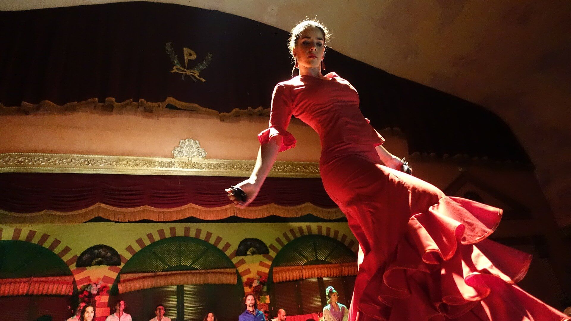 An image of a flamenco dance performer looking focused in her red dress mid performance